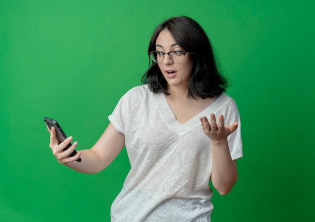 眼鏡をかけて携帯電話を持って見て、緑の背景で隔離の空の手を示している印象的な若いかなり白人の女の子