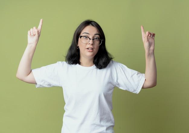 올리브 녹색 배경에 고립 가리키는 안경을 쓰고 감동 된 젊은 예쁜 백인 여자