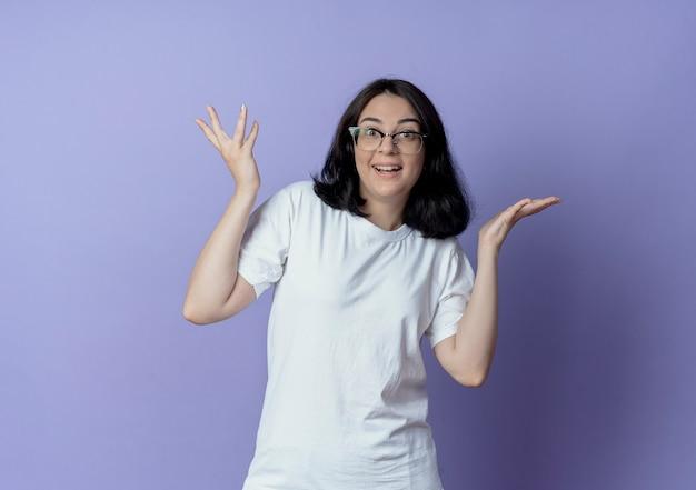印象深刻的年轻漂亮的白人女孩戴眼镜,显示空手孤立在紫色背景与复制空间