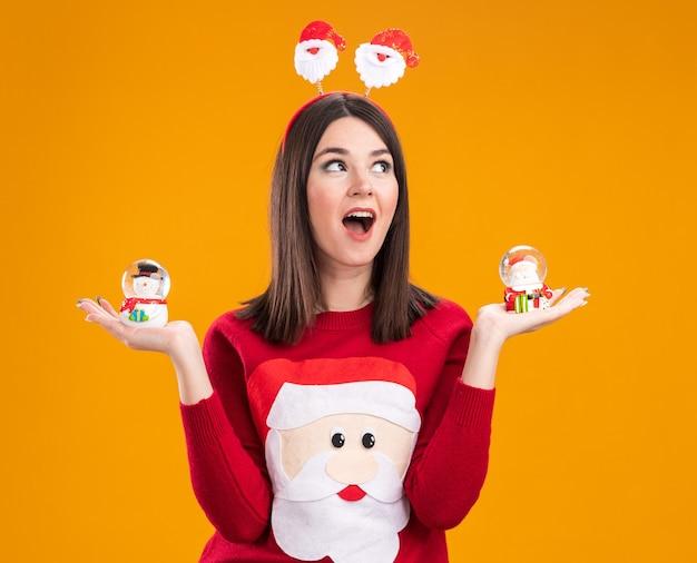 Impressionato giovane bella ragazza caucasica che indossa la fascia di babbo natale e un maglione che tiene pupazzo di neve e figurine di babbo natale guardando il lato isolato su sfondo arancione