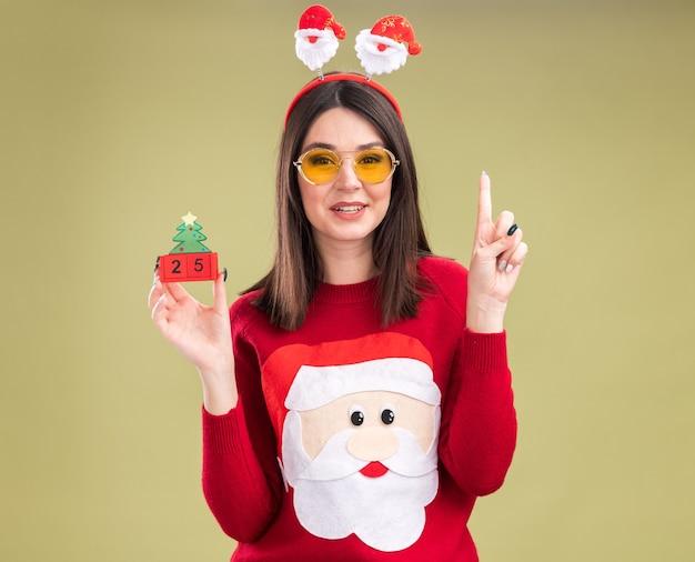 サンタクロースのセーターと日付のクリスマスツリーのおもちゃを保持しているメガネとヘッドバンドを身に着けている感動の若いかなり白人の女の子 無料写真