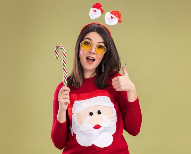 Впечатленная молодая симпатичная кавказская девушка в свитере санта-клауса и повязке на голову в очках, держащая традиционную рождественскую конфету