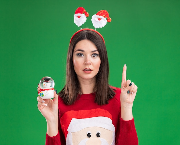 Impressed young pretty caucasian girl wearing santa claus sweater and headband holding snowman figurine  pointing up isolated on green wall