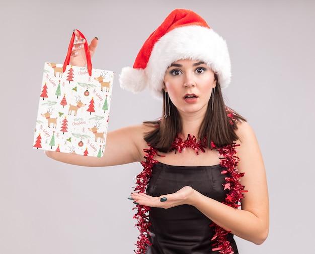 首の周りにサンタの帽子と見掛け倒しの花輪を身に着けて、白い背景で隔離のカメラを見てクリスマスギフトバッグを指して感動の若いかなり白人の女の子