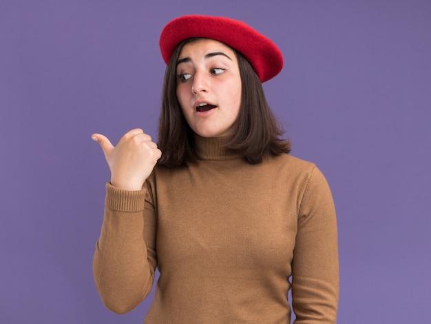 コピースペースで紫色の壁に隔離された側を見て、指しているベレー帽の帽子を持つ感銘を受けた若いかなり白人の女の子