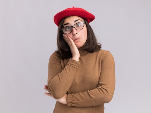 Impressionata giovane bella ragazza caucasica con berretto e occhiali ottici mette la mano sul viso isolato sul muro bianco con spazio per le copie