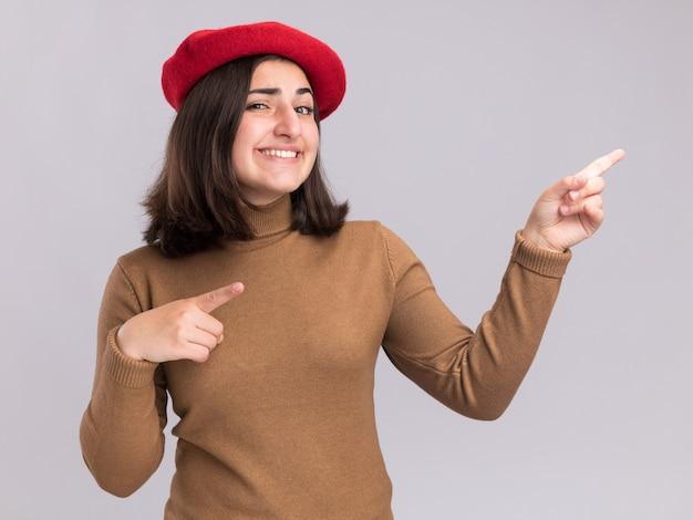 コピースペースで白い壁に分離された両手でベレー帽の帽子を横に向けている印象的な若いかなり白人の女の子