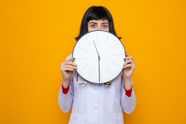 Impressionata giovane bella donna caucasica in uniforme da medico con uno stetoscopio che tiene l'orologio davanti al suo viso