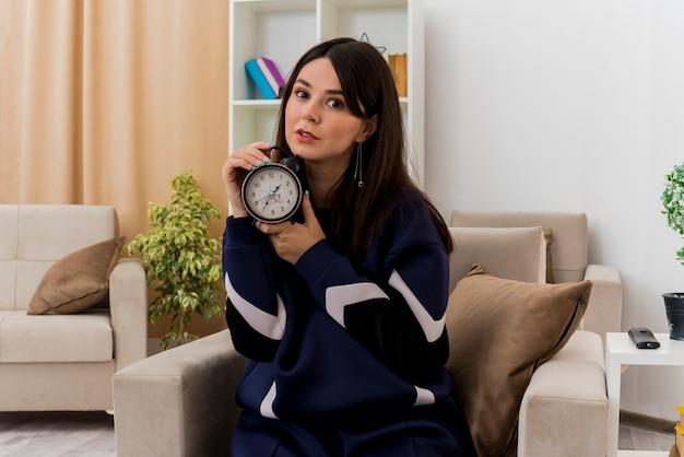 Impressionato giovane donna abbastanza caucasica seduto sulla poltrona nel soggiorno progettato tenendo la sveglia alla ricerca
