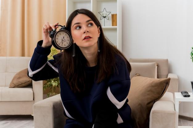 Impressionato giovane donna abbastanza caucasica che si siede sulla poltrona nel soggiorno progettato che tiene sveglia vicino all'orecchio guardando a lato