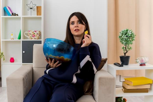 Impressionato giovane donna piuttosto caucasica seduto sulla poltrona nel soggiorno progettato tenendo una ciotola di patatine fritte e patatine fritte alla ricerca