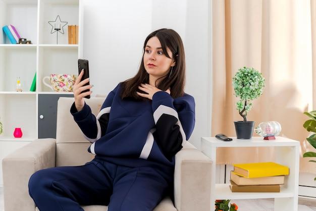Впечатленная молодая симпатичная кавказская женщина, сидящая на кресле в дизайнерской гостиной, держащая и смотрящую на мобильный телефон, держа руку на груди