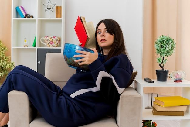 Впечатленная молодая симпатичная кавказская женщина, сидящая на кресле в дизайнерской гостиной, держащая миску чипсов и смотрящую на книгу