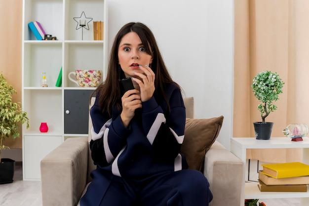 Впечатленная молодая симпатичная кавказская женщина, сидящая на кресле в дизайнерской гостиной, держащая пульт дистанционного управления и трогающая подбородок