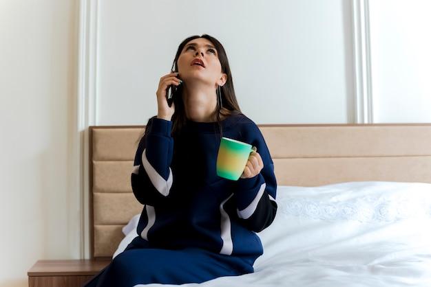 Впечатленная молодая симпатичная кавказская женщина, сидящая на кровати в спальне, держа чашку, глядя вверх и разговаривая по телефону