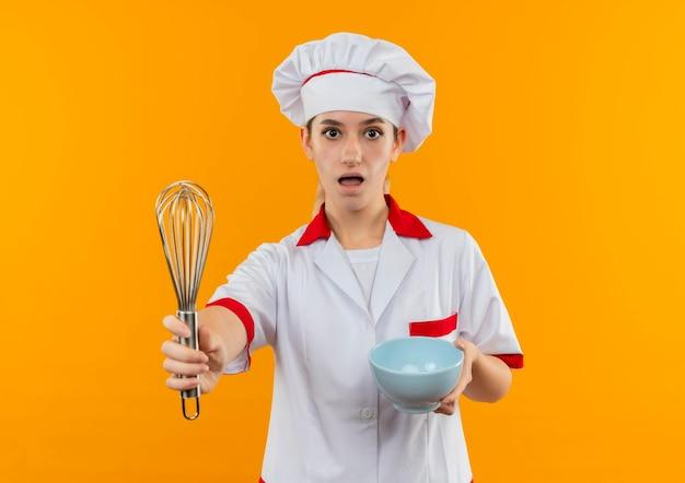Impressionato giovane e grazioso cuoco in uniforme da chef che tiene in mano una ciotola e allungando la frusta isolata sulla parete arancione