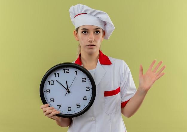 Impressionato giovane e graziosa cuoca in uniforme da chef che tiene l'orologio e mostra la mano vuota isolata sul muro verde