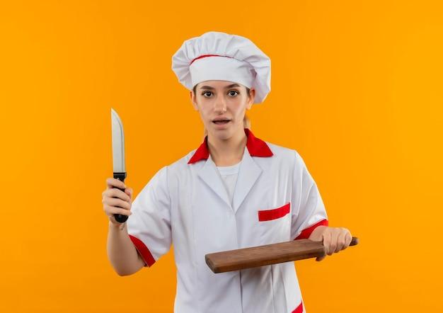 Impressionato giovane e graziosa cuoca in uniforme da chef con coltello e tagliere isolati su parete arancione