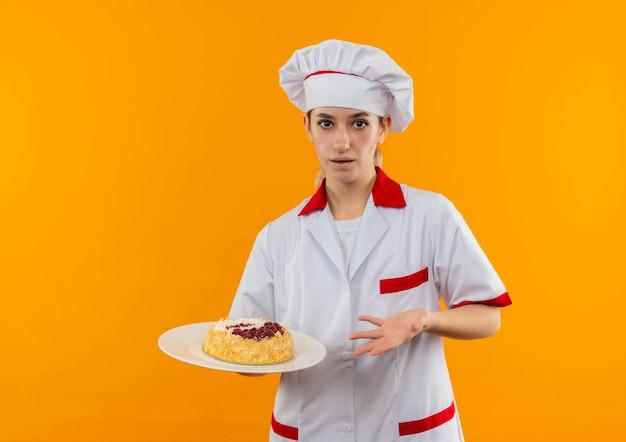 Impressionato giovane e graziosa cuoca in uniforme da chef che tiene e indica con la mano il piatto di torta isolato sulla parete arancione