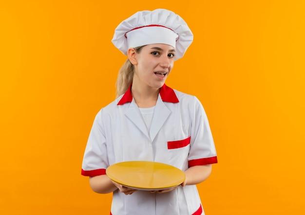 Impressionato giovane e graziosa cuoca in uniforme da chef con bretelle dentali che tengono piatto vuoto isolato su parete arancione
