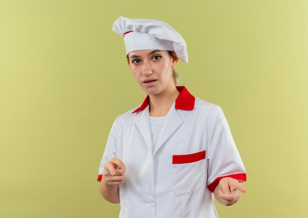 緑の壁にコピー スペースで隔離されたジェスチャーをしているシェフの制服を着た若いきれいな料理人に感銘