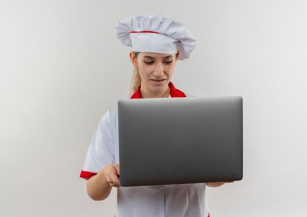 Впечатленный молодой симпатичный повар в форме шеф-повара, держащийся и смотрящий в ноутбук, изолированный на белой стене с копией пространства