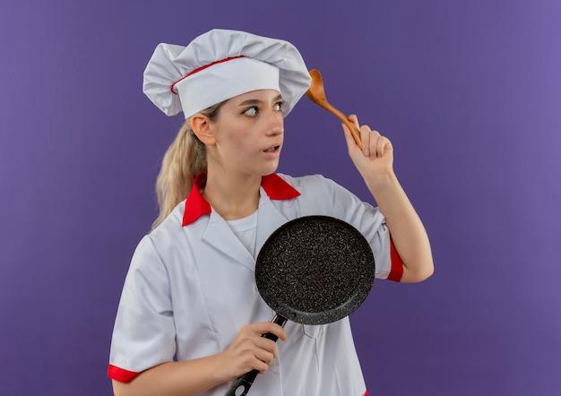 紫の壁に隔離された側を見て、フライパンとスプーンを保持しているシェフの制服を着た若いきれいな料理人に感銘