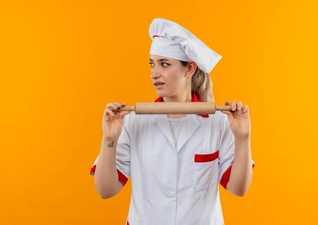 コピー スペースでオレンジ色の壁に分離された側を見て麺棒を保持しているシェフの制服を着た若いかわいい料理人