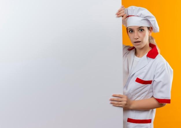後ろに立って、コピー スペースでオレンジ色の壁に分離された白い壁を保持しているシェフの制服を着た印象的な若いきれいな料理人