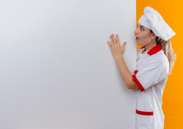 コピー スペースを持つオレンジ色の壁に分離された白い壁を見て、その上に手を置いて後ろに立っているシェフの制服を着た若いきれいな料理人に感銘を受けた