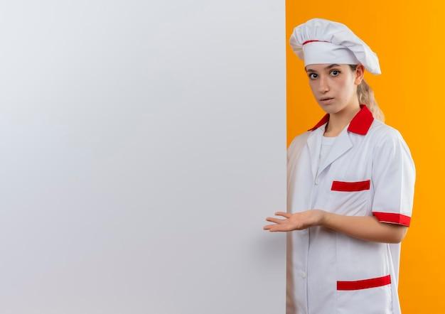 白い壁の後ろに立って、コピー スペースでオレンジ色の壁に分離された空の手を示すシェフの制服を着た若いきれいな料理人に感銘