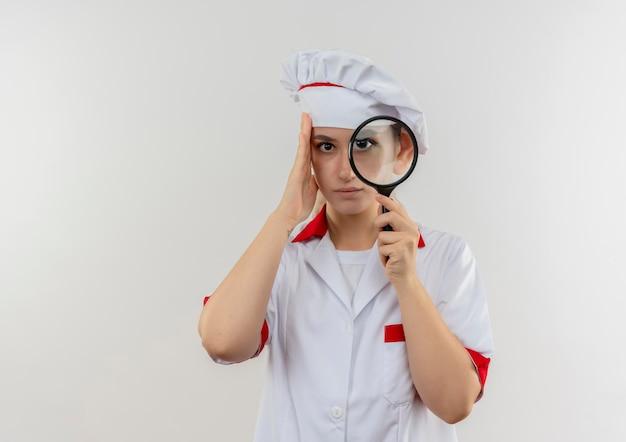 虫眼鏡を通してシェフの制服を着た若いきれいな料理人に感銘を受け、コピースペースのある白い壁に手を置いて頭に置く