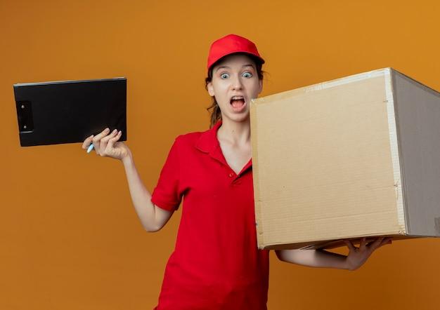 Впечатленная молодая симпатичная доставщица в красной форме и кепке, держащая ручку и буфер обмена с картонной коробкой, смотрящей вниз, изолированной на оранжевом фоне