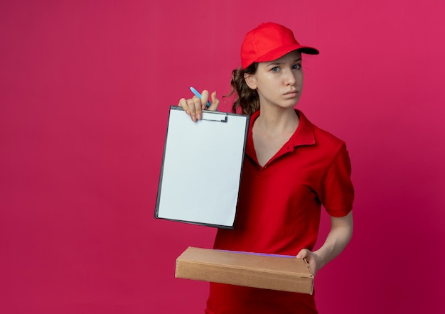 Впечатленная молодая симпатичная доставщица в красной форме и кепке, держащая ручку пакета пиццы и показывающая буфер обмена, изолированный на малиновом фоне с копией пространства
