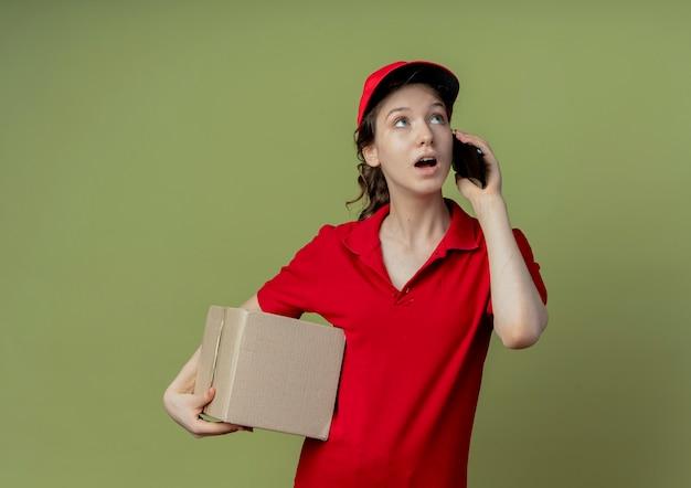 Впечатленная молодая симпатичная доставщица в красной форме и кепке, глядя вверх, держа картонную коробку и разговаривая по телефону, изолированную на оливково-зеленом фоне с копией пространства
