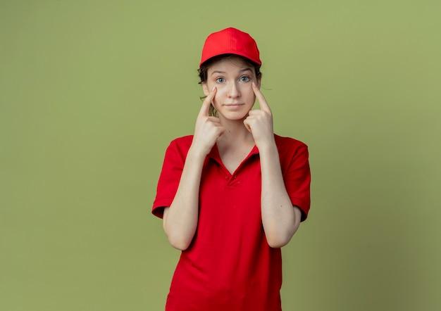 Впечатленная молодая симпатичная доставщица в красной форме и кепке, положив пальцы под глаза, изолированные на оливково-зеленом фоне с копией пространства