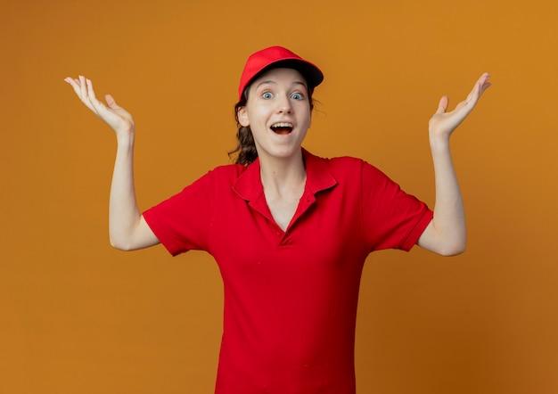 빨간 유니폼과 모자 오렌지 배경에 고립 된 빈 손을 보여주는 감동 된 젊은 예쁜 배달 소녀