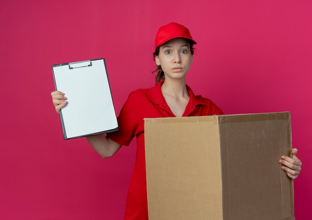 Impressed young pretty delivery girl in red uniform and cap holding carton box and clipboard isolated on crimson background