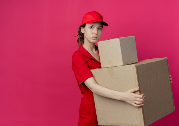 Impressed young pretty delivery girl in red uniform and cap holding carton boxes isolated on crimson background with copy space