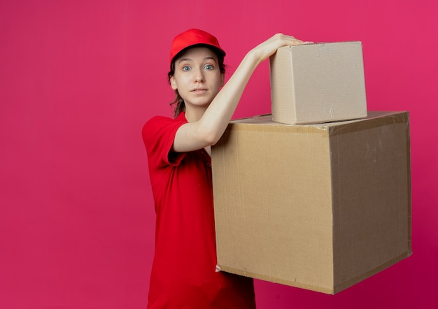 Impressed young pretty delivery girl in red uniform and cap holding carton boxes looking at camera isolated on crimson background with copy space