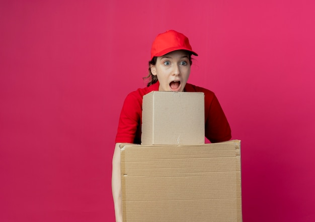 Impressed young pretty delivery girl in red uniform and cap holding carton boxes looking straight isolated on crimson background with copy space