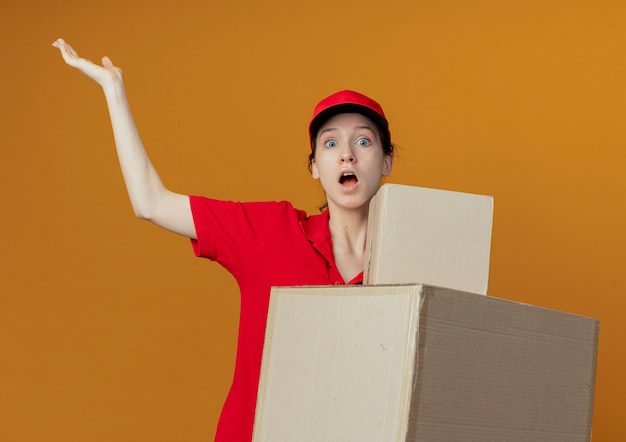 Impressed young pretty delivery girl in red uniform and cap holding carton boxes and showing empty hand isolated on orange background