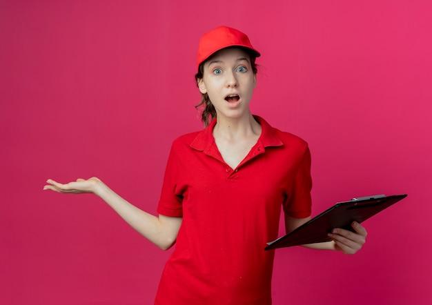 Impressionato giovane ragazza graziosa di consegna in uniforme rossa e berretto che tiene appunti e mostrando la mano vuota isolata su sfondo cremisi
