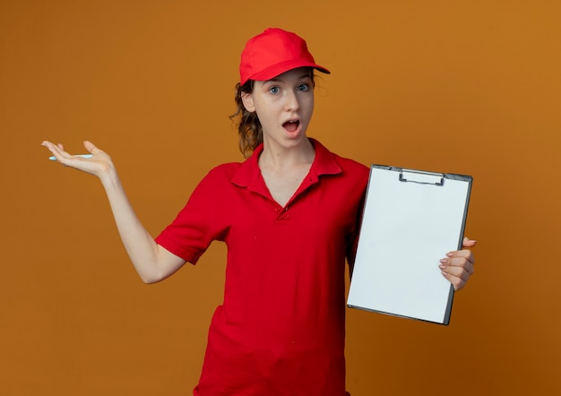 Impressed young pretty delivery girl in red uniform and cap holding pen and clipboard and pointing with hand at side isolated on orange background