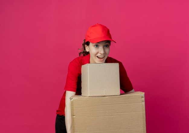 Impressed young pretty delivery girl in red uniform and cap looking straight holding carton boxes isolated on crimson background with copy space