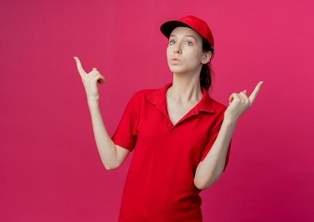 Impressionato giovane bella consegna ragazza in uniforme rossa e berretto guardando dritto e rivolto verso l'alto isolato su sfondo cremisi con spazio di copia