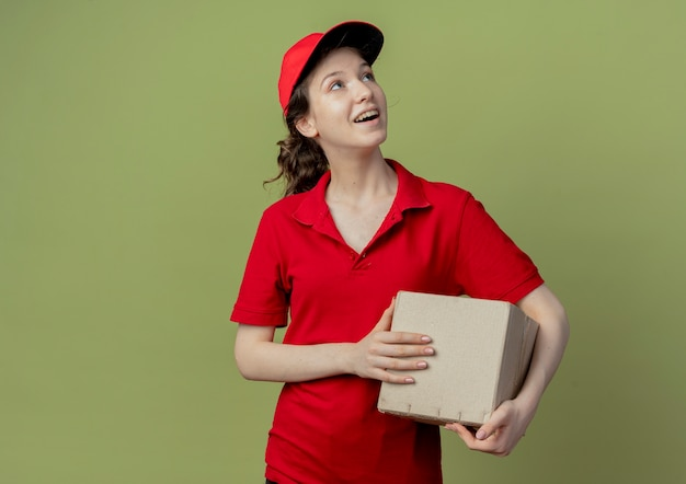 Impressed young pretty delivery girl in red uniform and cap looking up and holding carton box isolated on olive green background with copy space
