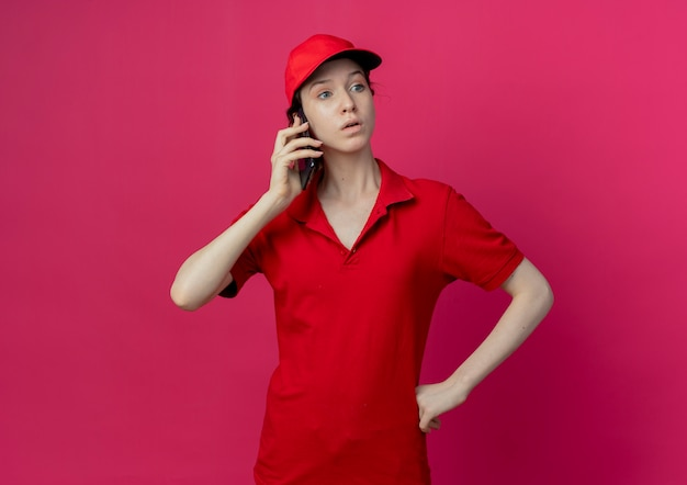 Impressed young pretty delivery girl in red uniform and cap talking on phone looking at side with hand on waist isolated on crimson background with copy space