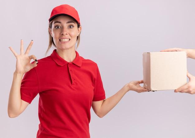 La giovane ragazza graziosa di consegna impressionata in segno giusto della mano di gesti uniformi e dà il cardbox a qualcuno su bianco