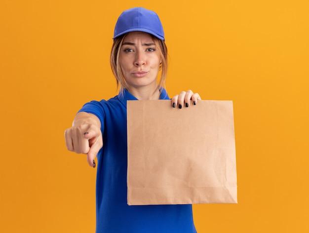 La giovane ragazza graziosa di consegna impressionata in uniforme tiene il pacchetto di carta e indica la macchina fotografica sull'arancio